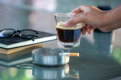 a hand holding a glass of black coffee and cigarette smoking on the table with the books and the glasses. relaxing time bad habits lifestyle, unhealthy lifestyle