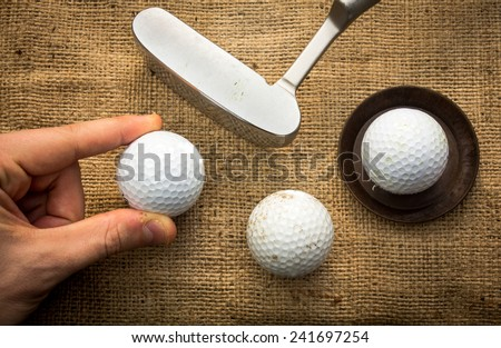 A hand holding a golf ball near a putter and two other golf balls