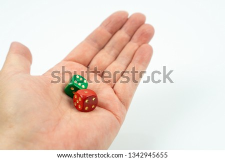 A hand holding a green dice and a red dice, white background #1342945655