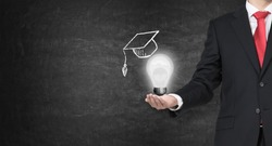 A hand holding a mortarboard with a light bulb, concept of education.