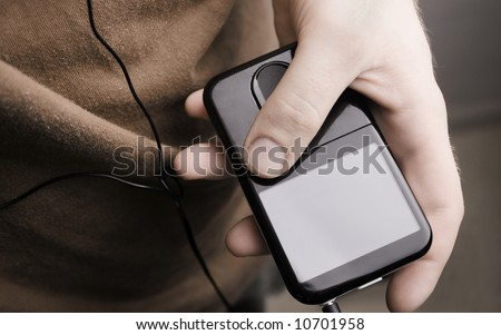 A hand holding a MP3 player. Screen can be used to hold text.
