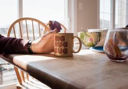 A hand holding a mug with the slogan big hug mug at home