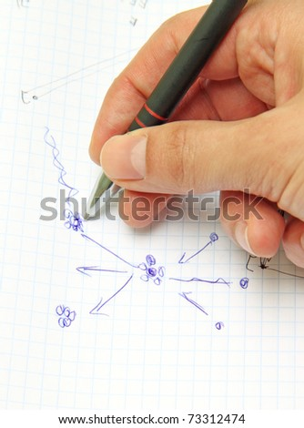 A hand holding a pen and sheet of paper with drawn nuclear reactions