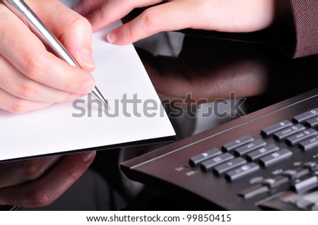 A hand, holding a pen, is ready to write on a document with a telephone next to it.