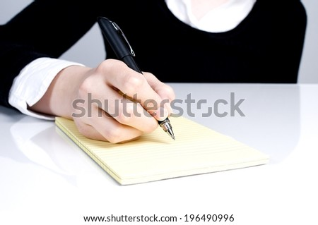 A hand holding a pen over a lined pad of paper.
