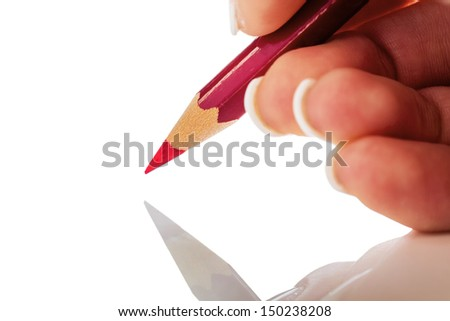a hand holding a red pen. symbolic photo for savings and budegt cuts.