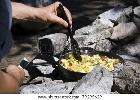 A hand holding a spatula, cooking breakfast over a campfire.