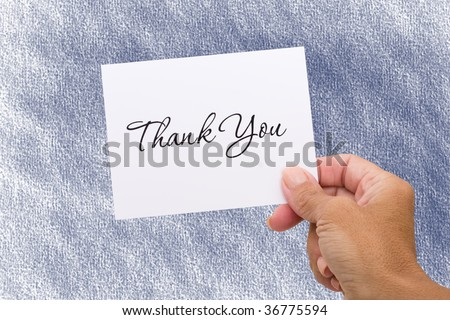A hand holding a thank you card on a blue background, thank you card