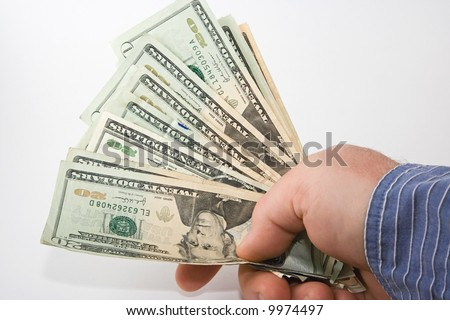 A hand holding a wad of cash, in twenties