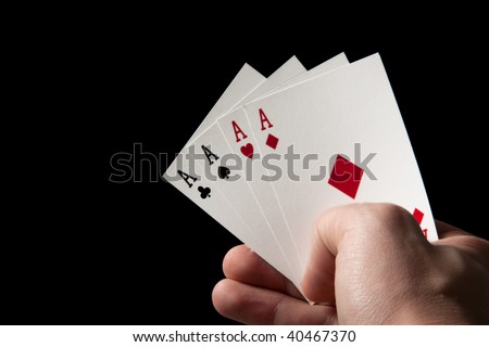 A hand holding all four aces in a pack of cards.  Low key on a black background.