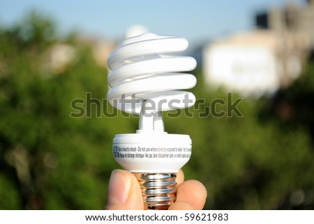 A hand holding an energy efficient light bulb against the backdrop of an urban park.