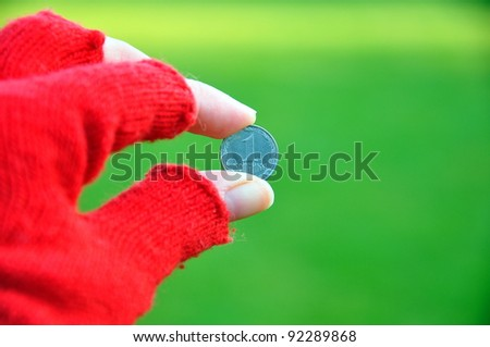 a hand holding coin between fingers