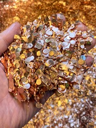 A hand holding copper scrap in a recycling plant