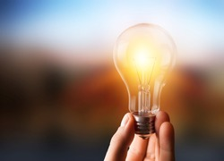 A hand holding is light bulb for save energy. Creative ideas concept, lightbulb for new idea, object design for thinking          - Image