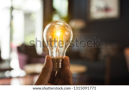 A hand holding is light bulb for save energy. Creative ideas concept, lightbulb for new idea, object design for thinking