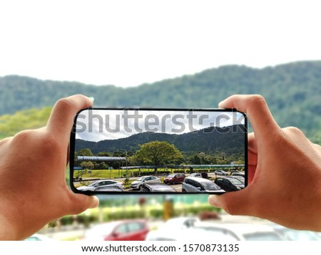 A hand holding mobile photo to take photo.