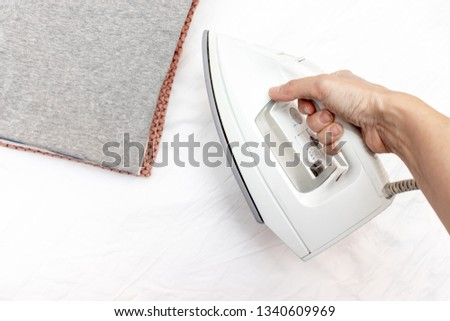 A hand holding modern electrical white iron ready to iron a stack of clothes - ironing, laundry and housework concept. #1340609969