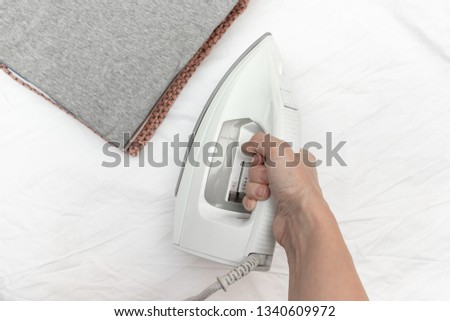 A hand holding modern electrical white iron ready to iron a stack of clothes - ironing, laundry and housework concept. #1340609972