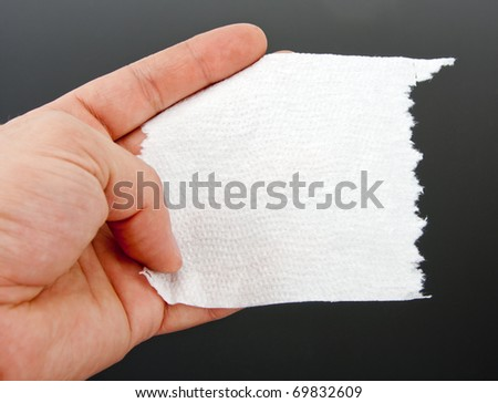 A hand holding one piece of toilet paper. Close-up
