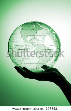 A hand holding translucent globe