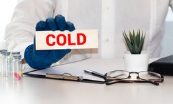 A Hand Holding Wooden Letters Spelling Out The Word Cold. Passing On A Virus Concept.