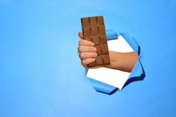 A hand holds a bar of chocolate through a hole in the blue torn paper. Special offer and cheap price for confectionery. Copy space.
