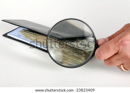 a hand holds a magnifying glass in front of cash in a check book