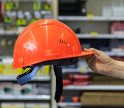 A hand holds a red construction helmet in a large supermarket. Blurred background