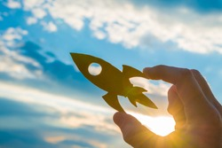 A hand holds a rocket against the sky. Business concept idea, Promotion. takeoff, success, quick start.