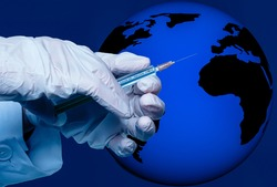 a hand holds a syringe with the inscription covid 19 vaccine in front of globe