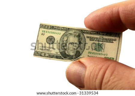 a hand holds miniature money representing the world financial crisis isolated on white