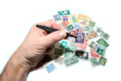 A hand holds one stamp in the pincer. Several other stamps are lying below. Philately is a hobby or also investment.