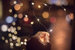 A hand holiding lights of a hear shape with bokeh on the background