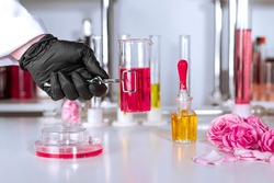 A hand in a glove holding a clip with a test tube in up-to-date perfume laboratory. Background blurred.