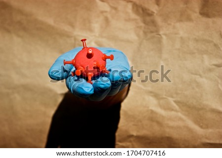 A hand in a medical protective glove holds in his palm an abstract 2019-nCoV coronavirus infection strain. Stay at home. Self-isolation during quarantine as a way to stay safe during the coronavirus p Stock fotó ©