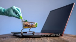 A hand in a sterile medical glove holds a shopping cart with a credit card for online purchases. Concept of internet purchasing important life support products during the coronavirus pandemic