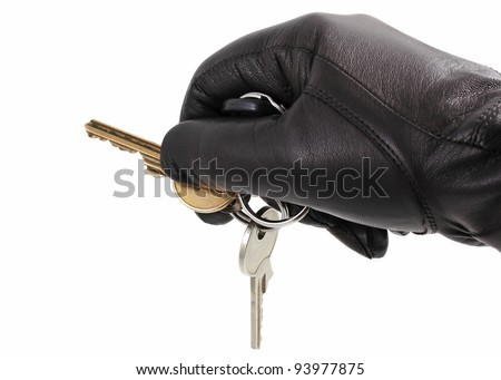 A hand in black glove with  keys on white background