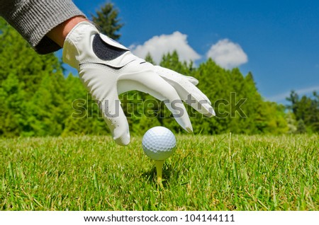 A hand in the golf glove placing golf ball on the tee with  nice golf course and  blue sky as a background