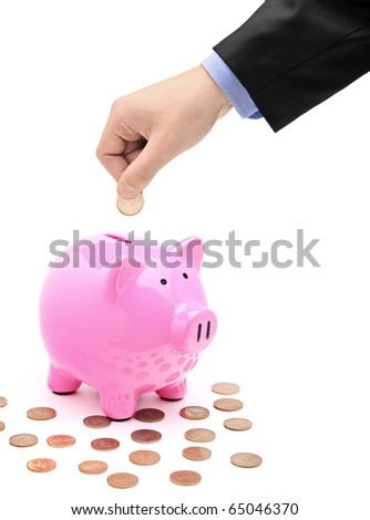 A hand inserting a coin into a pink piggy bank isolated against white background