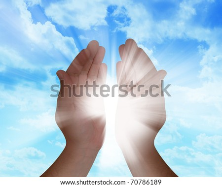 A hand is catching the sun rays in their hands with clouds in the background.