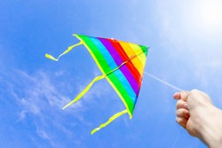 A hand is holding a rope, multi-colored stripes of a rainbow kite flying high in a clear blue sky with the sun. The concept of dreams, freedom, childhood, happiness, success. Festive background.