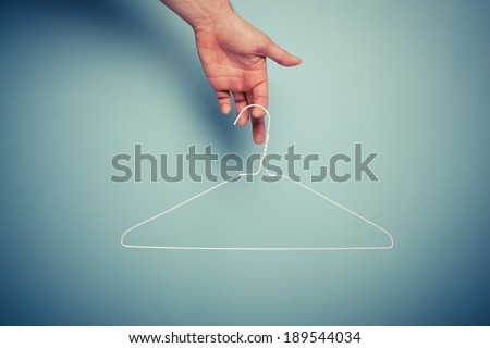 A Hand is holding a wire hanger