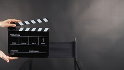 A hand is holding black clapper board or movie slate and director chair on black background. It has written in number.
