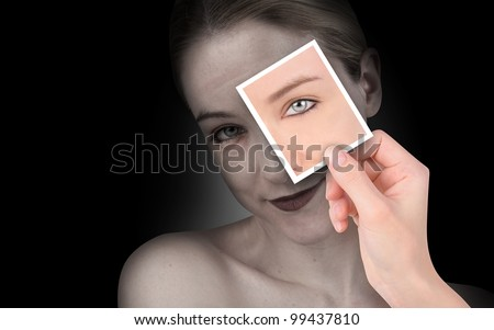 A hand is holding up a photo of a young eye on a wrinkled woman's face. She is isolated on a black background. Use to represent time or aging.