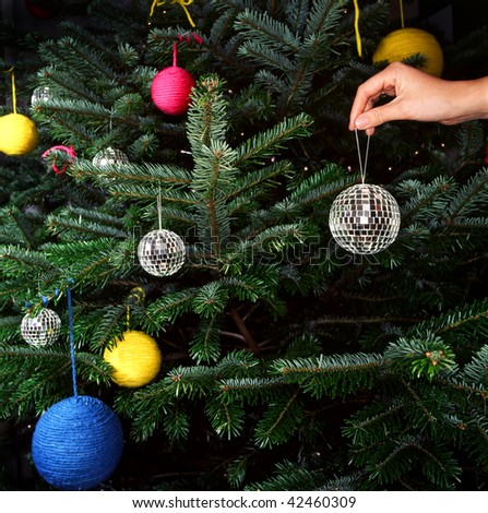 A hand is shown putting a disco ball ornament on a Christmas tree. Square format.