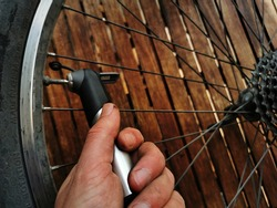 A hand manipulating a bicycle tire for mending, maintenance and repair of a flat mountain bike tube. Using an air pump. Wooden workbench in background.