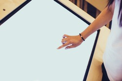 A hand of a assistant typing on a blank large display of a professional tablet in bank or exhibition. Concept of business assistance, type your text.