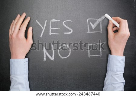 A hand of a businesswoman makes a Yes choice with chalk on a blackboard. Top view.