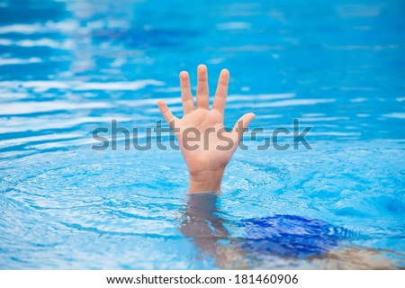 A hand of a drowning person stretching out of the water in a swimming pool asking for help. Stress concept.