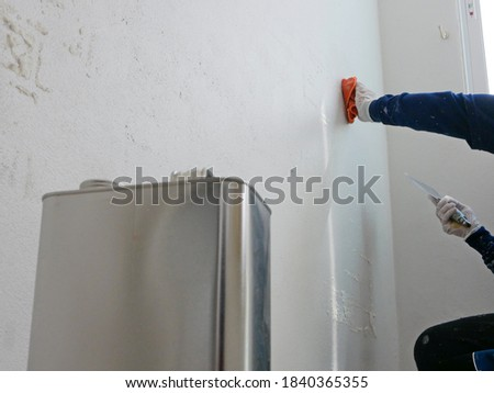 A hand of a painter holding on a piece of cloth, soaked with thinner, removing sticky rough glue and tape remain on the old concrete wall, as a preparation before starting the paint the house Stock photo ©
